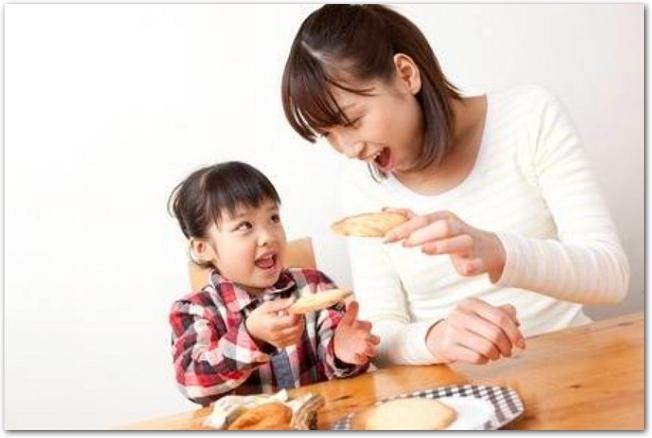 クッキーを食べる女の子と若い母親