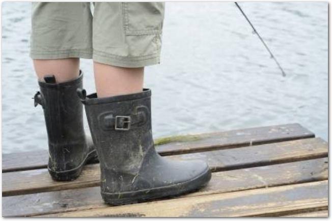 釣竿を持つ少年の足元はブーツを履いている