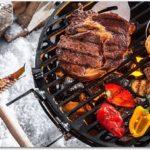 雪の上に置かれたバーベキューグリルで野菜と肉を焼いている様子