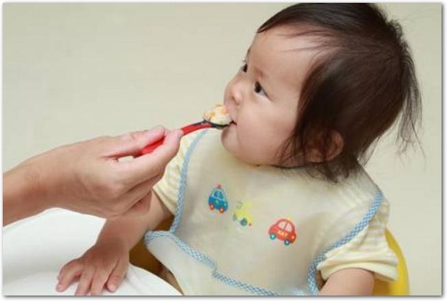 離乳食を食べさせられている女の子