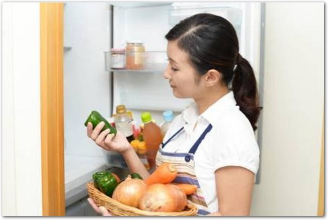 冷蔵庫の前で野菜を片手に悩んでいる女性