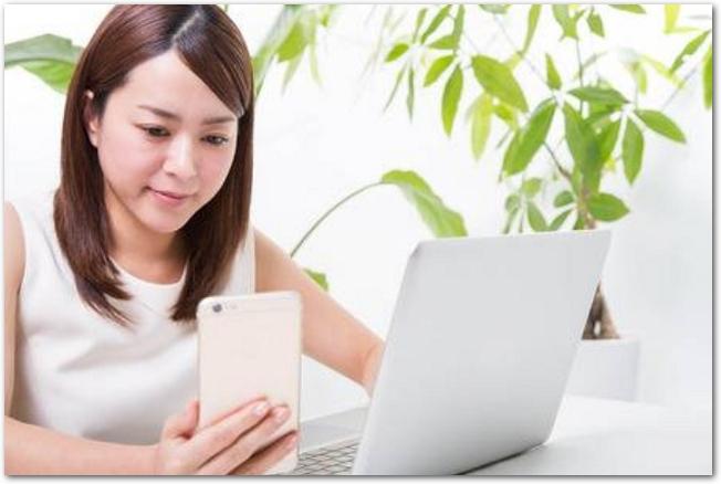 スマホとパソコンの画面を見ている若い女性